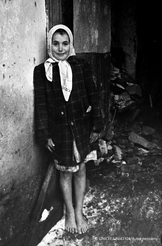Československo, 1946: Bosé 9-ročné dievčatko stojí na snehu pred vojnou poškodeným domom v meste Rožňave.